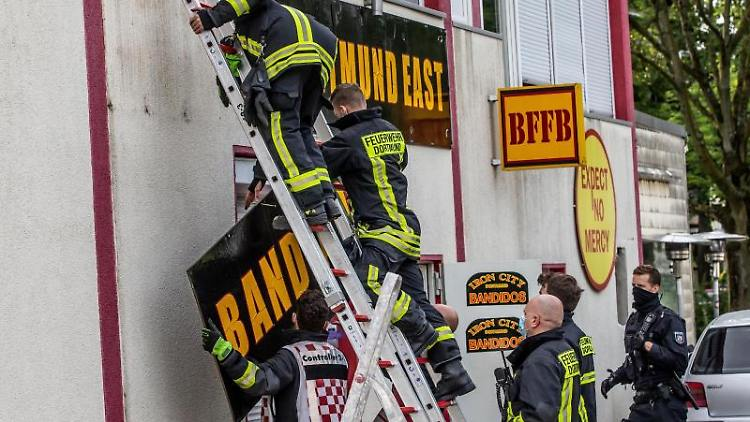 Feuerwehrleute entfernen unter Polizeischutz ein Schild am Vereinsheim der Rockergruppe