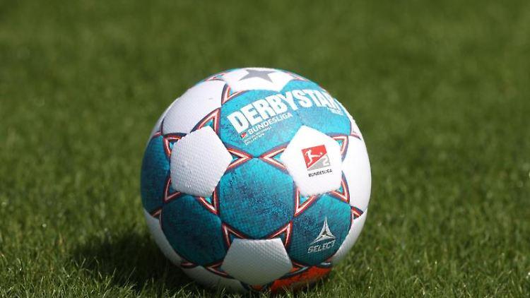 Ein Fußball liegt auf dem Rasen. Foto: Guido Kirchner/dpa/Symbolbild