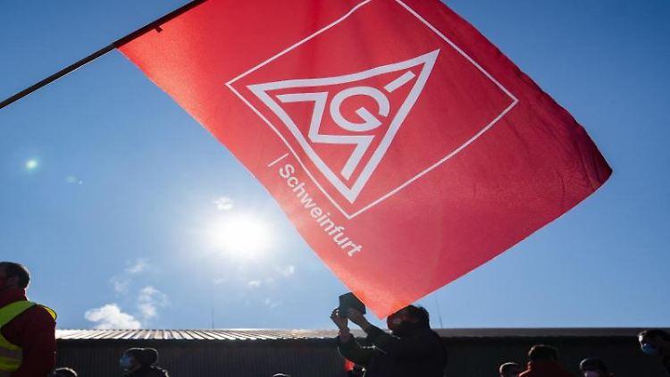 EinTeilnehmer eines Warnstreicks schwenkt eine Fahne mit demLogo der IGMetall. Foto: Nicolas Armer/dpa/Symbolbild