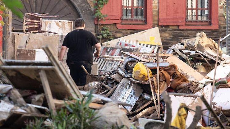 Anwohner laufen in der Innenstadt von Ahrweiler durch Unrat und aufgetürmte Einrichtungsgegenstände aus den zerstörten Häusern und Wohnungen. Foto: Boris Roessler/dpa