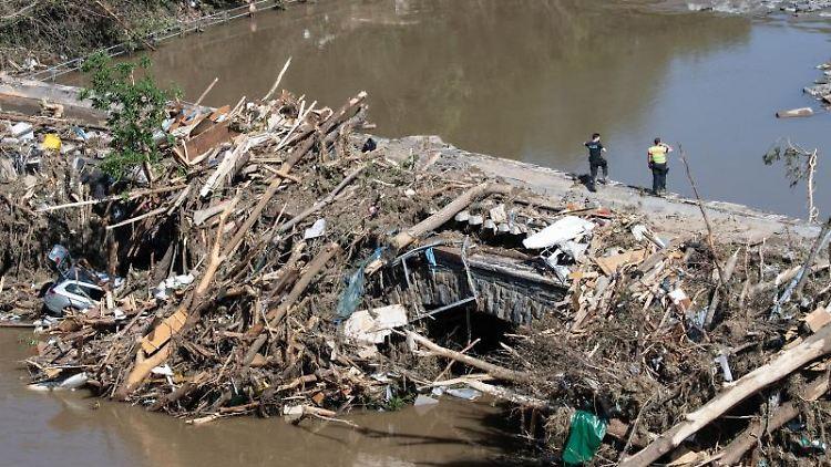 Polizisten suchen im Geröll an einer Ahrbrücke nach möglichen Opfern der Flutkatastrophe. Foto: Boris Roessler/dpa