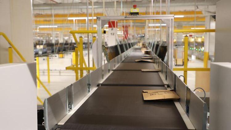 Amazon-Versandkartons liegen auf Transportbändern bei einem Probebetrieb in einer Logistikhalle. Foto: Bodo Schackow/dpa-zentralbild/dpa