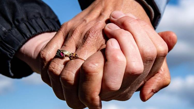 Eine Frau und ein Mann halten sich bei einem Spaziergang an den Händen. Foto: Axel Heimken/dpa/Symbolbild