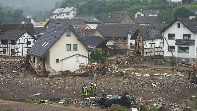 Feuerwehrleute stehen in der Gemeinde Schuld am Tag nach der Hochwasserkatastrophe in Trümmern. Foto: Thomas Frey/dpa/Archivbild