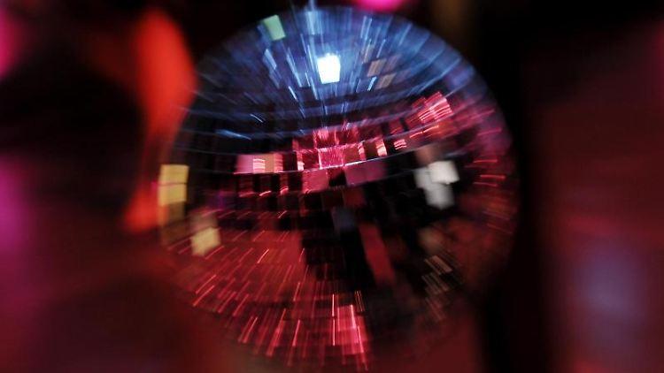Scheinwerferlicht spiegelt sich in einer Discokugel. Foto: picture alliance / dpa/Symbolbild