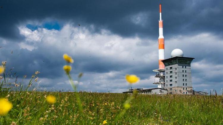 Dunkle Wolken ziehen über die Brockenherberge mit Funkturm auf dem Brocken im Harz. Foto: Swen Pförtner/dpa