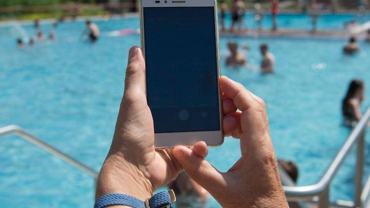 Eine Frau hält im Freibad ein Smartphone in Richtung des Pools. Foto: Sebastian Kahnert/dpa-Zentralbild/dpa/Symbolbild