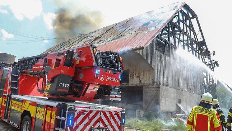 Einsatzkräfte der Feuerwehr stehen vor einer Scheune die in voller Ausdehnung brennt. Foto: Thomas Warnack/dpa