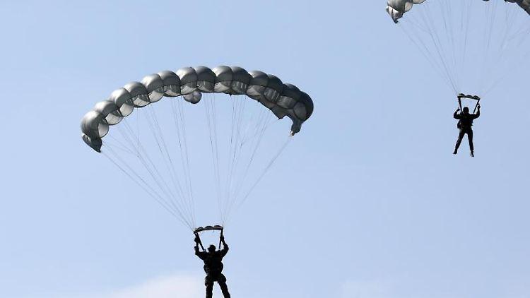 Fallschirmspringer aus Niedersachsen springen bei einer Übung mit Gleitschirmen. Foto: Bernd Wüstneck/dpa-Zentralbild/dpa/Archivbild