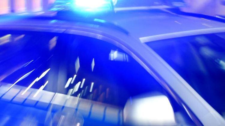 Ein Streifenwagen der Polizei steht mit eingeschaltetem Blaulicht auf der Straße. Foto: Carsten Rehder/dpa/Illustration