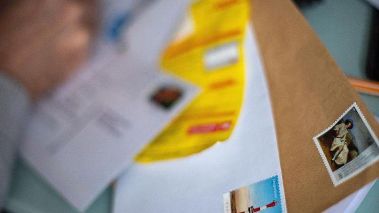 Frankierte Briefumschläge liegen auf einem Tisch. Foto: Monika Skolimowska/dpa-Zentralbild/dpa/Symbolbild