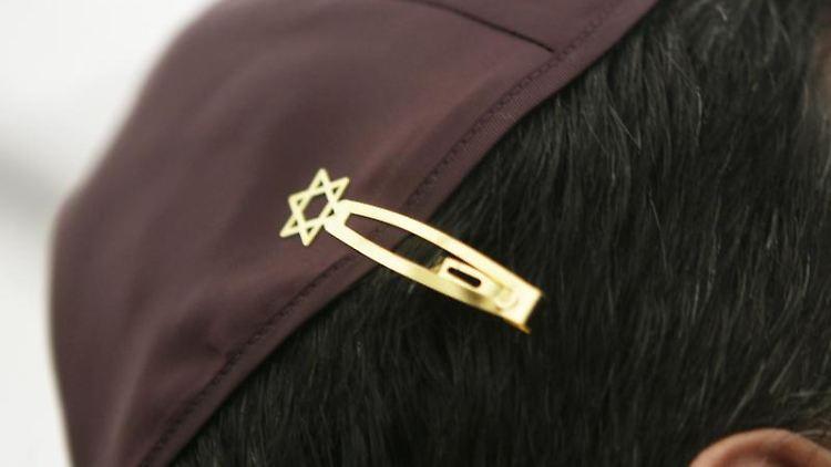 Ein Jude hat sich bei den Feierlichkeiten einer Grundsteinlegung für eine Synagoge seine Kippa mit einer Davidstern-Klammer am Haar befestigt. Foto: Fredrik von Erichsen/dpa/Archivbild