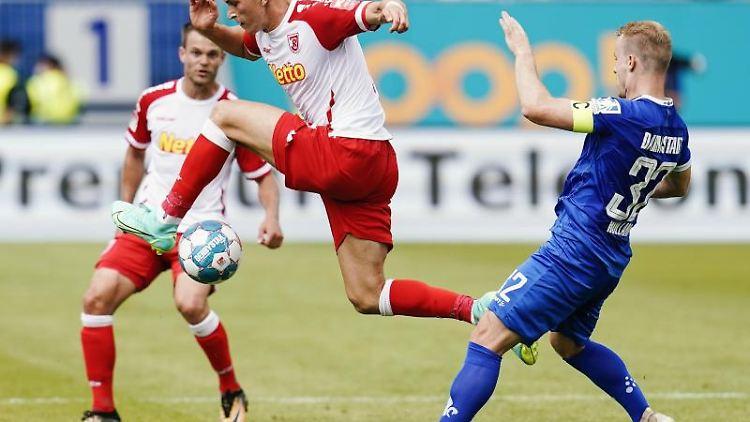 Regensburgs David Otto (l) und Darmstadts Fabian Holland kämpfen um den Ball. Foto: Uwe Anspach/dpa
