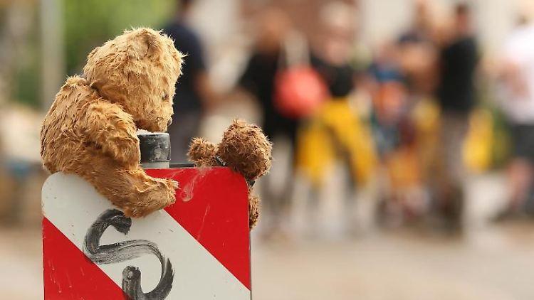 Zwei nasse Teddybären trocknen auf einem Straßenschild. Foto: David Young/dpa/Archivbild