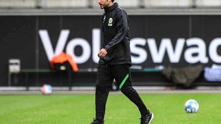 Wolfsburgs Trainer Mark van Bommel geht über das Spielfeld. Foto: Swen Pförtner/dpa/Archivbild