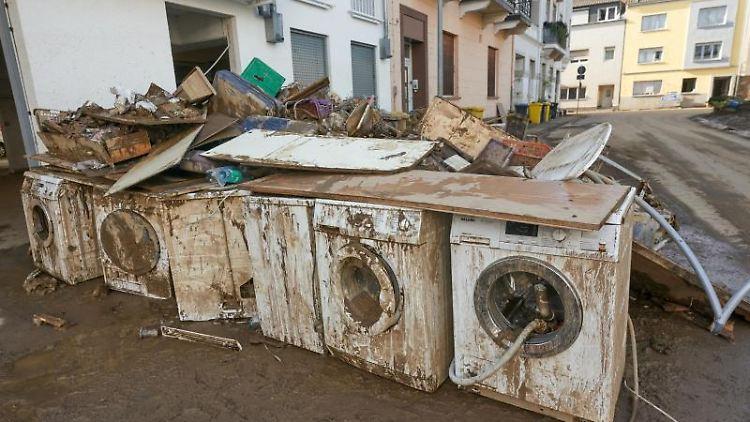 Zerstörte Waschmaschinen stehen vor einem Wohnhaus. Foto: Thomas Frey/dpa