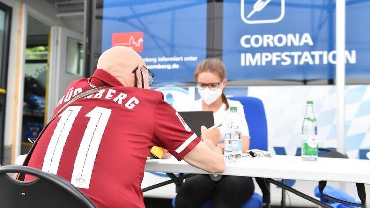 Ein Fan vom 1. FC Nürnberg füllt vor dem Spiel gegen Erzgebirge Aue an einem Impfbus ein Formular zur Impfung gegen Covid-19 aus. Foto: Timm Schamberger/dpa