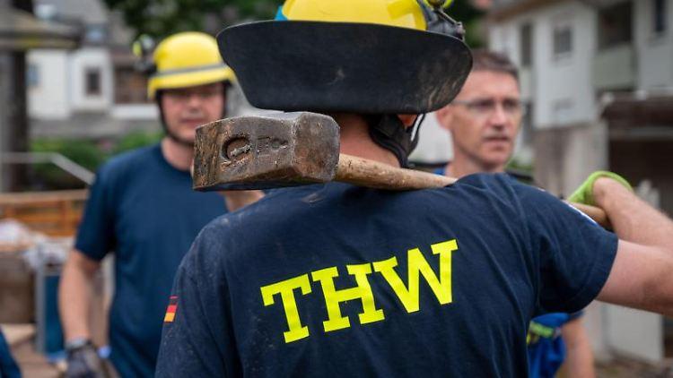 Ein THW-Helfer steht mit einem Vorschlaghammer. Foto: Harald Tittel/dpa
