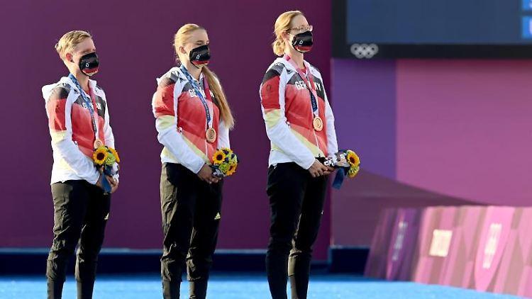 Michelle Kroppen, Charline Schwarz und Lisa Unruh feiern mit der Bronzemedaille bei der Siegerehrung. Foto: Swen Pförtner/dpa