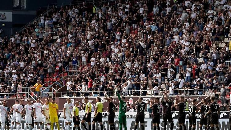 Die Spieler beider Mannschaften begrüßen die Zuschauer im Stadion. Foto: Axel Heimken/dpa