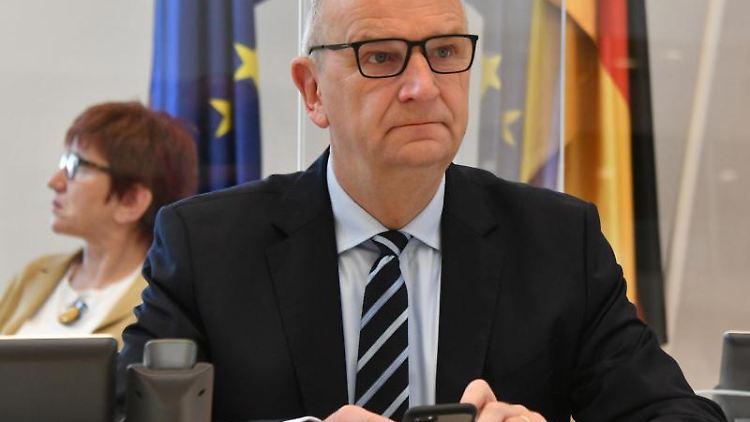 Dietmar Woidke (SPD, r), Ministerpräsident von Brandenburg, sitzt im Landtag. Foto: Bernd Settnik/dpa
