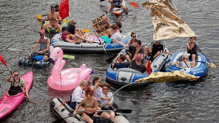 Demonstranten fahren während der Schlauchbootregatta unter dem Motto
