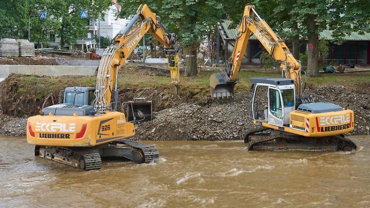 Bagger reißen Teile einer durch die Flut zerstörte Brücke über der Ahr ab. Foto: Thomas Frey/dpa/Archivbild