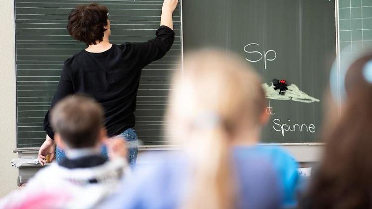 Eine Lehrerin schreibt etwas an die Tafel. Foto: Sebastian Gollnow/dpa/Symbolbild
