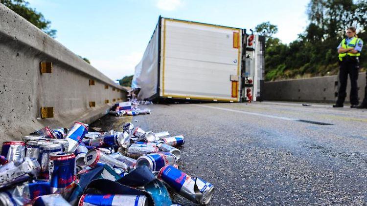 Energiedrinkdosen liegen vor einem umgekippten Lastwagen auf der A45. Foto: Alex Talash/dpa
