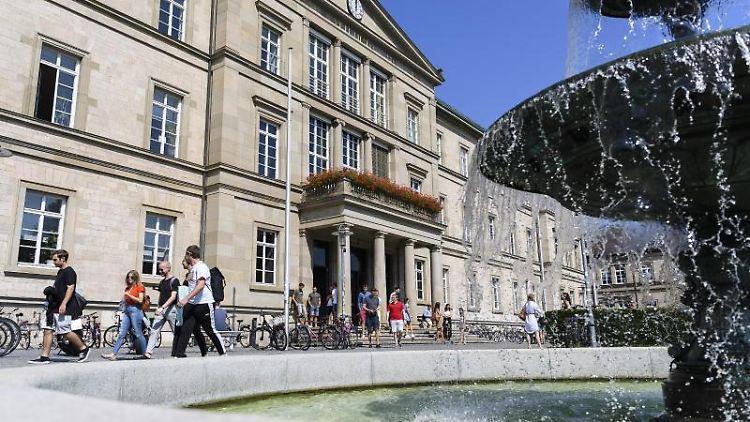 Studentinnen und Studenten laufen vor der Universität Tübingen an einem Brunnen vorbei. Foto: Edith Geuppert/dpa/archivbild