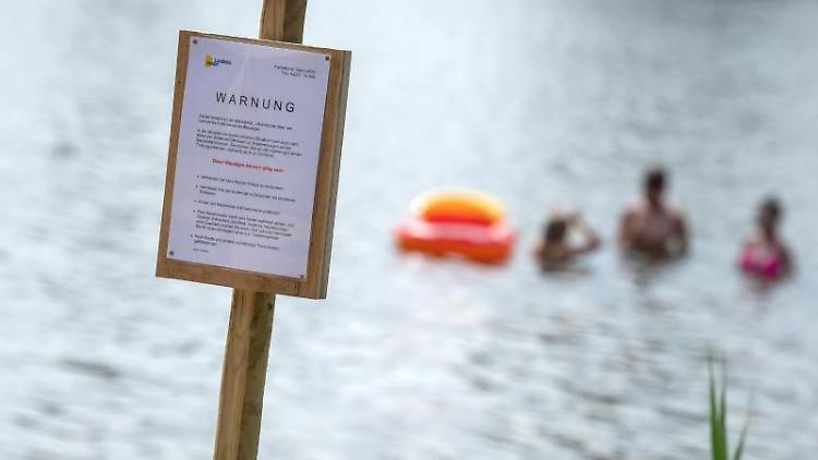 Ein Schild an einem See warnt vor Blaualgen. Foto: Sina Schuldt/dpa/Symbolbild