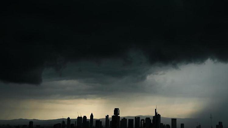 Tiefschwarze Gewitterwolken verdunkeln den Himmel über Frankfurt am Main. Foto: Arne Dedert/dpa/Archivbild
