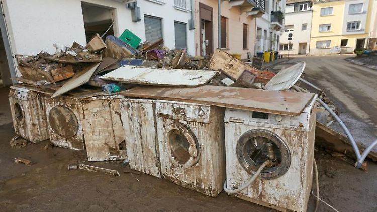Zerstörte Waschmaschinen stehen vor einem Wohnhaus in Bad Neuenahr-Ahrweiler. Foto: Thomas Frey/dpa