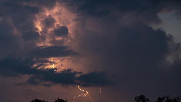 Ein Blitz hellt hinter dunklen Wolken auf. Foto: Fabian Sommer/dpa