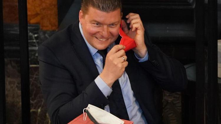 Andreas Dressel (SPD), Senator für Finanzen in Hamburg, setzt sich eine FFP2-Maske auf. Foto: Marcus Brandt/dpa/Archivbild