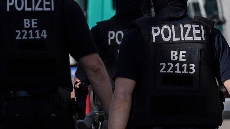 Berliner Polizisten gehen über eine Straße. Foto: Paul Zinken/dpa/Symbolbild