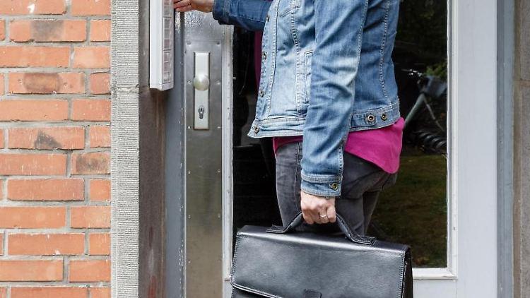 Eine Gerichtsvollzieherin klingelt an einem Hauseingang. Foto: Markus Scholz/dpa/Symbolbild