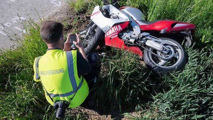 Ein Mitarbeiter der Unfallforschung hockt vor einem verunfallten Motorrad. Foto: Julian Stratenschulte/dpa/Symbolbild