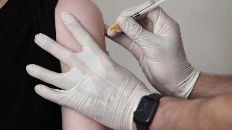 Ein Hausarzt impft einen Jugendlichen in seiner Praxis. Foto: Oliver Berg/dpa/Symbolbild
