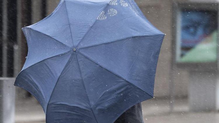 Ein Passant geht bei Nieselregen durch die Stadt. Foto: Boris Roessler/dpa/Symbolbild