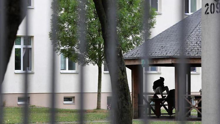 Ein Asylsuchender sitzt vor einem Wohnblock im Ankerzentrum. Foto: Karl-Josef Hildenbrand/dpa/Archivbild