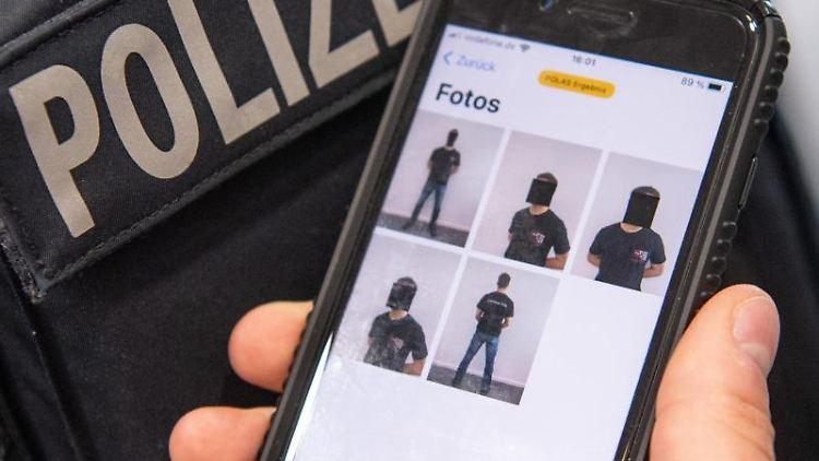 Ein Polizist zeigt auf seinem Smartphone eine spezielle Polizei-App. Foto: Boris Roessler/dpa