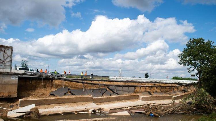 Arbeiter inspizieren Teile der infolge des Hochwassers unterspülten und eingestürzten Autobahn A1. Foto: Jonas Güttler/dpa