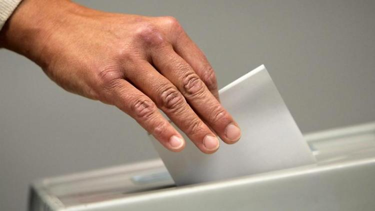 Eine Frau wirft einen den Stimmzettel in die Urne. Foto: picture alliance / Fredrik Von Erichsen/dpa/Symbolbild