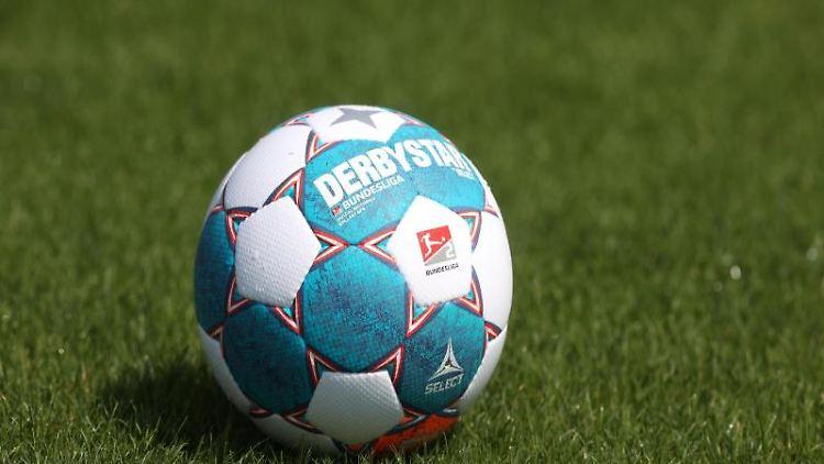 Der Spielball liegt auf dem Rasen. Foto: Guido Kirchner/dpa/Symbolbild