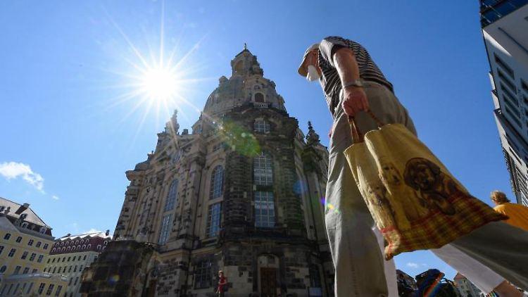 Menschen, die Masken tragen, laufen auf dem Neumarkt vor der Frauenkirche entlang. Foto: Robert Michael/dpa-Zentralbild/dpa/Archivbild