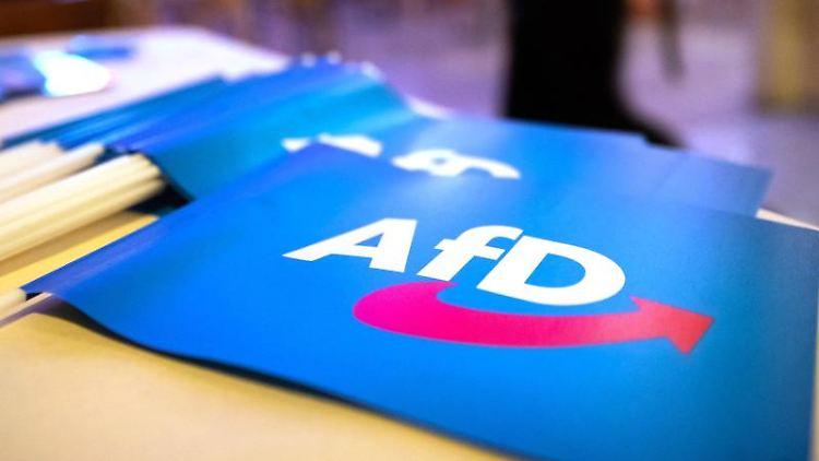 Fähnchen mit dem Logo der AfD liegen auf einem Tisch. Foto: Daniel Karmann/dpa/Symbolbild
