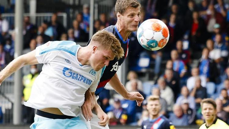 Schalkes Marius Bülter (l) und Kiels Patrick Erras kämpfen um den Ball. Foto: Frank Molter/dpa