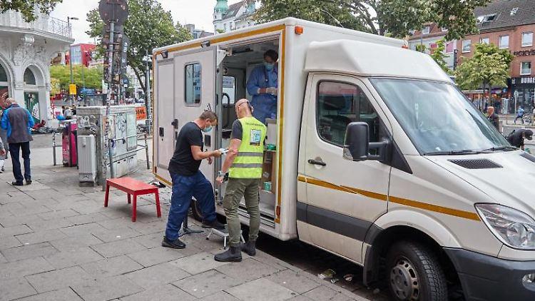 Ein Obdachloser steigt auf der Reeperbahn in das Gesundheitsmobil. Foto: Georg Wendt/dpa