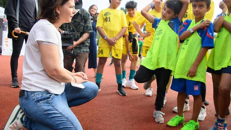 Annalena Baerbock (l), Kanzlerkandidatin von Bündnis 90/Die Grünen, unterhält sich mit den Kindern. Foto: Soeren Stache/dpa-Zentralbild/dpa